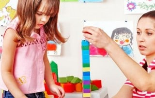 image of nanny playing stacking blocks with child